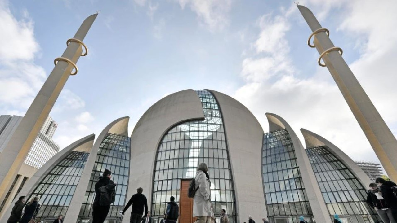 Orang-orang berdiri di luar masjid pusat DITIB pada 'Hari Pembukaan Masjid' di Cologne, Jerman. (Associated Press)